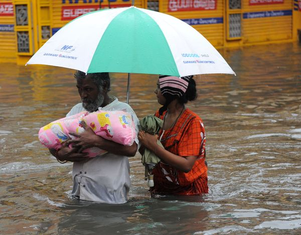 An Indian family wade through floodwaters in Chennai on Dec. 2, 2015.