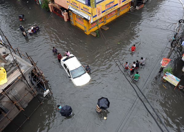 Indian residents attempt to push a vehicle through floodwaters as others wade past in Chennai on Dec. 2, 2015. India has depl