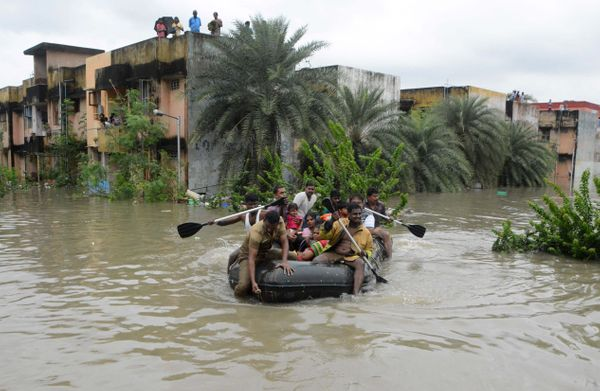 Indian rescue personnel and police officials paddle an inflatable boat through floodwaters as they evacuate residents in Chen