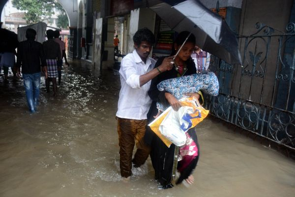 An Indian couple shelter under an umbrella as they walk with their child through floodwaters inundating Egmore Hospital in Ch