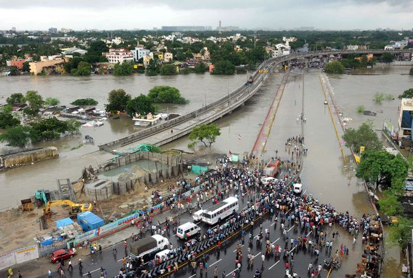 Indian bystanders and travelers gather as floodwaters lap at the end of a highway in Chennai on Dec. 2, 2015.