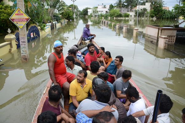 Indian rescue workers on a boat move people to safety amid water-logged houses in a flooded suburb of Chennai on Nov. 17, 201