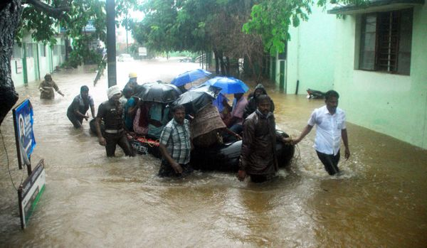 Indian rescue workers and volunteers use an inflatable boat to take residents through floodwaters in Chennai on Dec. 1, 2015.