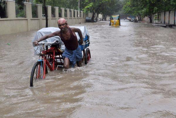 An Indian laborer pushes his cycle trishaw through floodwaters in Chennai on Dec.1, 2015.