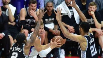 Blake Griffin of the Los Angeles Clippers looks to pass under pressure from Kawhi Leonard and Tim Duncan of the San Antonio Spurs during Game 5 of their first round NBA playoffs series in Los Angeles, California on April 28, 2015.  AFP PHOTO / FREDERIC J. BROWN        (Photo credit should read FREDERIC J. BROWN/AFP/Getty Images)
