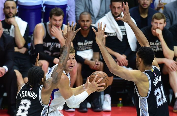 The Clippers' Blake Griffin looks to pass under pressure from theSpurs' Kawhi Leonard and Tim Duncan.