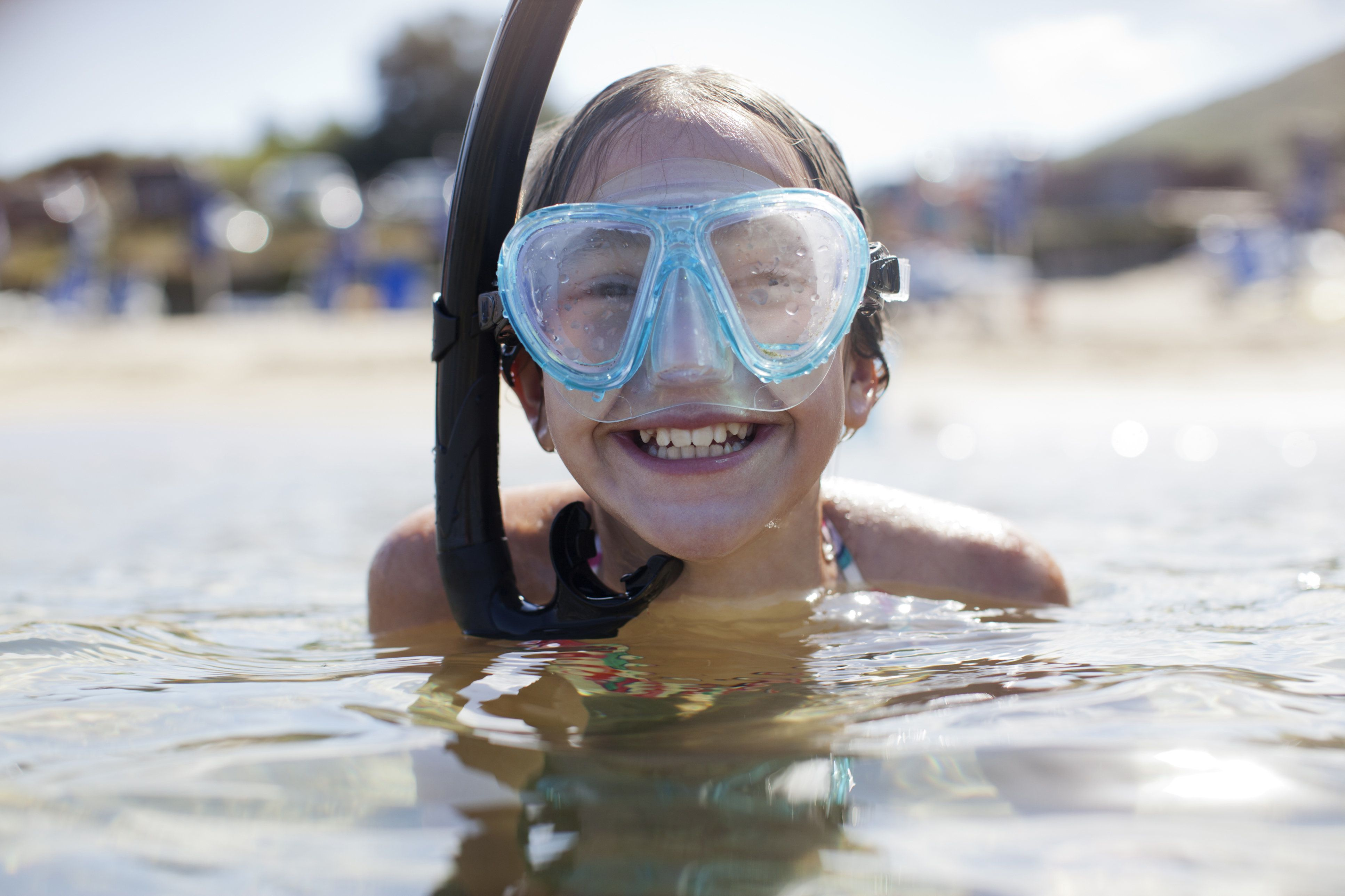 Happy girl wearing snorkel and goggles in ocean