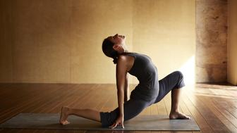Yoga instructor showing advanced poses in intimate yoga studio