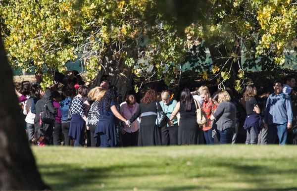 SAN BERNARDINO, CA - DECEMBER 2, 2015: Evacuated workers pray in a circle on the San Bernardino Golf Course across the