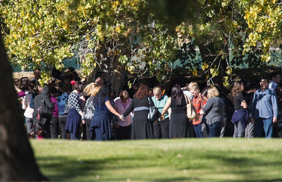 Evacuated workers pray in a circle on the San Bernardino Golf Course across the street where a mass shooting occurred at the