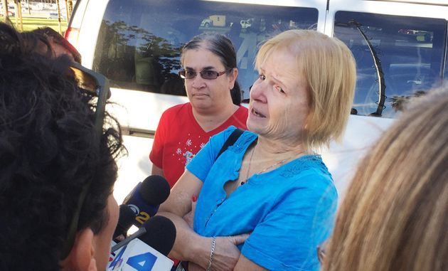 Sherry Esquerra with daughter Angel (in red) speaks to reporters near the shooting scene in San Bernardino,...