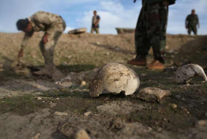 Members of the Kurdish military investigate a mass grave they say contains the remains of more than 50 Yazidis who were kille