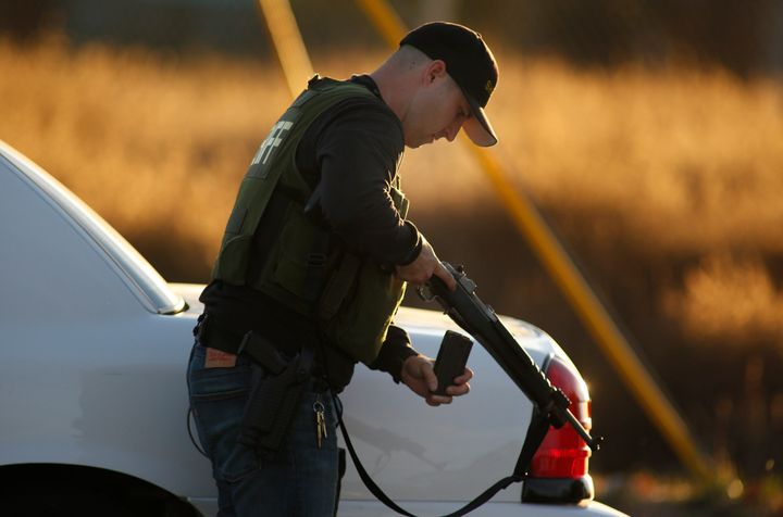 A police officer checking his weapon during the pursuit of suspects afterthe deadly shooting in San Bernardino.
