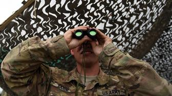 TO GO WITH AFGHANISTAN-US-ARMY-CONFLICT-FOCUS BY GUILLAUME DECAMME In this photograph taken on August 12, 2015, a US army soldier looks on with binoculars at Coalition forces Forward Operating Base (FOB) Connelly in Khogyani district in the eastern province of Nangarhar. From his watchtower in insurgency-wracked eastern Afghanistan, US army Specialist Josh Whitten doesn't have much to say about his Afghan colleagues. 'They don't come up here anymore, because they used to mess around with our stuff. 'Welcome to Forward Operating Base Connelly, where US troops are providing training and tactical advice to the 201st Afghan army corps as they take on the Taliban on the battlefield. AFP PHOTO / Wakil Kohsar        (Photo credit should read WAKIL KOHSAR/AFP/Getty Images)