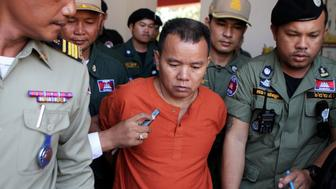 Unlicensed Cambodian doctor Yem Chroeum (C) is escorted by Cambodian police officials as he walks at a court in Battambang province, western Cambodia, on December 3, 2015.  An unlicensed Cambodian doctor was sentenced to 25 years in prison on December 3 after he was found guilty of infecting more than 200 people with HIV, including some who later died.   AFP PHOTO   CAMBODIA OUT / AFP / STR        (Photo credit should read STR/AFP/Getty Images)