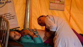 TO GO WITH Nepal-quake-health-children,FEATURE by Ammu Kannampilly In this photograph taken on July 15, 2015, a Nepalese villager is monitored by a health worker at a makeshift birthing centre in the village of Gerkhu in Nuwakot, north of Kathmandu. Some 70 percent of clinics that had been providing crucial services to pregnant women were severely damaged in the Nepalese districts hardest hit by the 7.8 magnitude quake on April 25.   AFP PHOTO / Prakash MATHEMA        (Photo credit should read PRAKASH MATHEMA/AFP/Getty Images)