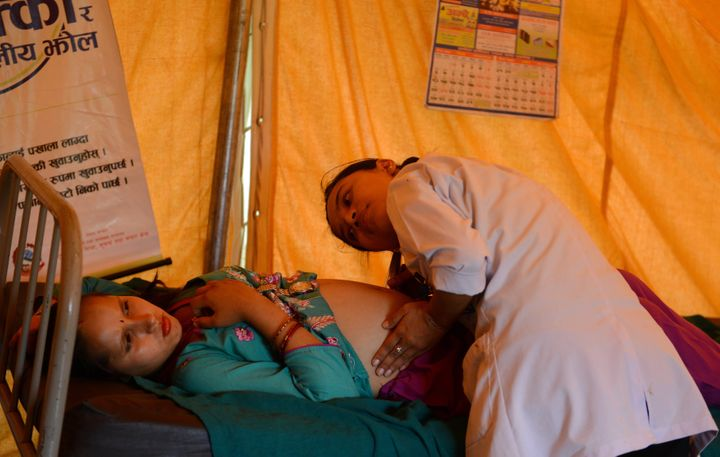 In this photograph taken on July 15, 2015, a Nepalese villager is monitored by a health worker at a makeshift birthing centre