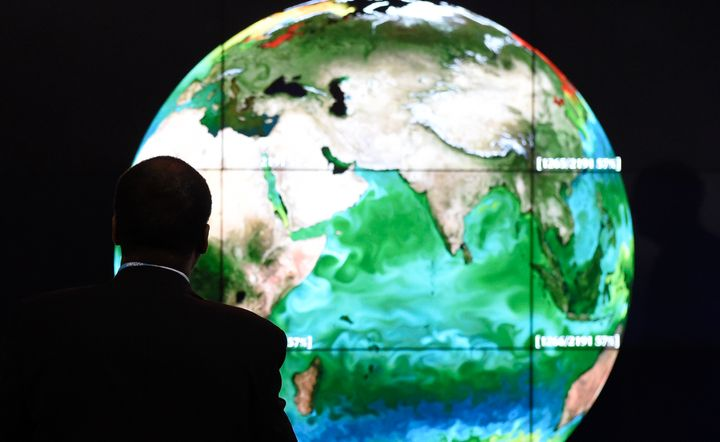 A conference attendee studies a projection of the Earth on the first day of the COP21 United Nations conference on clima