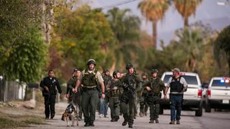 SAN BERNARDINA, CA - DECEMBER 2:  A search team goes door-to-door looking for the third suspect in a residential neighborhood after a mass shooting  at the Inland Regional Center on December 2, 2105 in San Bernardino, California. Multiple fatalities and injuries were reported as police search for up to three suspects who are still at-large. (Photo by Marcus Yam/Los Angeles Times via Getty Images)
