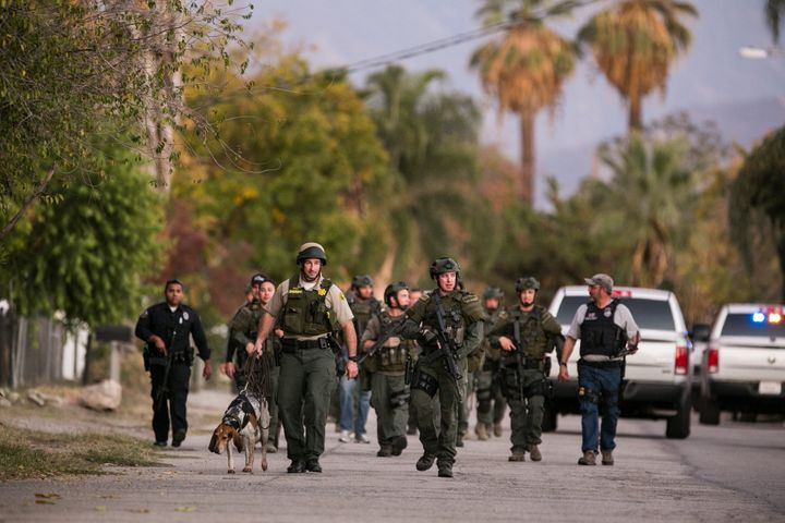 A search team goes door-to-door looking for the third suspect in a residential neighborhood after the mass shooting in S