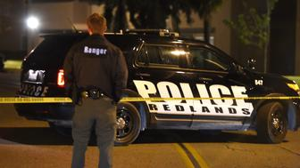 An officer stands guard at the police perimeter in a Redlands, California neighborhood where a home linked to  the suspects in the San Bernardino shooting rampage is located, in the early hours of December 3, 2015.  A heavily armed man and woman killed at least 14 people and injured at least 17 at a social services center in nearby San Bernardino on December 2, 2015 before the suspects died during a shootout with police.  AFP PHOTO /ROBYN BECK / AFP / ROBYN BECK        (Photo credit should read ROBYN BECK/AFP/Getty Images)
