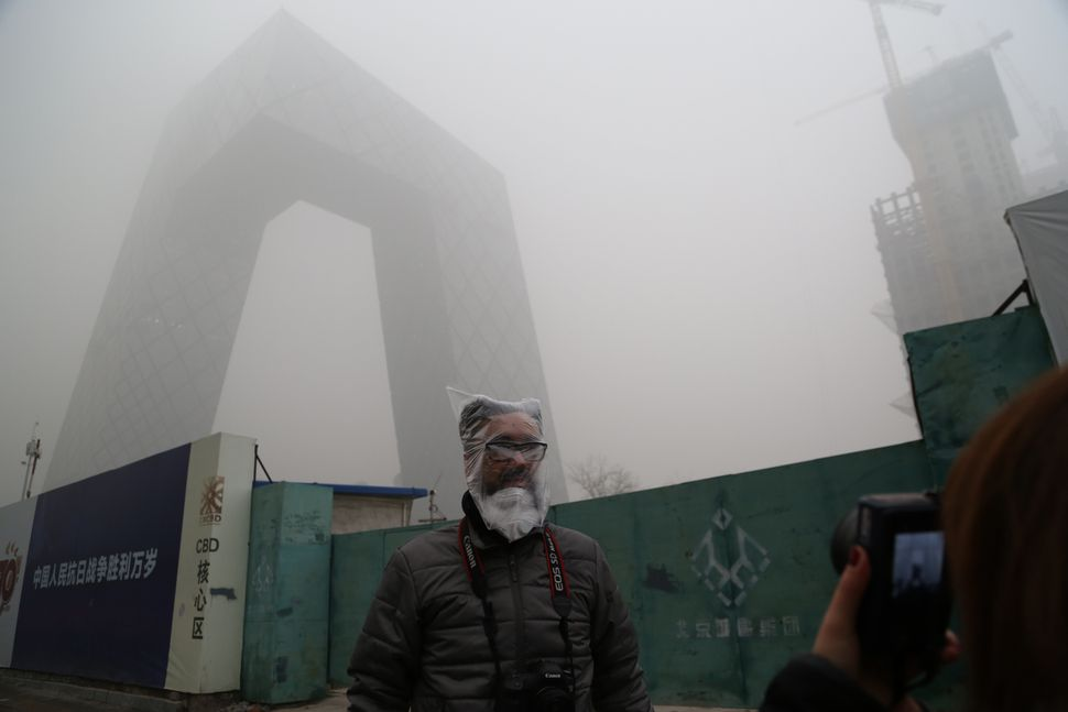 A man wearing a plastic bag stands in front of the CCTV Headquarters in the heavy smog on December 1, 2015 in Beijing, China.