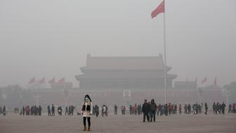 BEIJING, CHINA - NOVEMBER 30:A  Chinese woman wears a mask as she walks through a very hazy Tiananmen Square on a day of heavy pollution on November 30, 2015 in Beijing, China. China's capital and many cities in the northern part of the country recorded the worst smog of the year with air quality devices in some areas unable to read such high levels of pollutants. Levels of PM 2.5, considered the most hazardous, crossed 600 units in Beijing, nearly 25 times the acceptable standard set by the World Health Organization. The governments of more than 190 countries are meeting in Paris this week to set targets on reducing carbon emissions in an attempt to forge a new global agreement on climate change.  (Photo by Kevin Frayer/Getty Images)