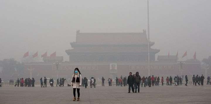 A Chinese woman wears a mask as she walks through a very hazy Tiananmen Square on a day of heavy pollution in Beijing on Nov.