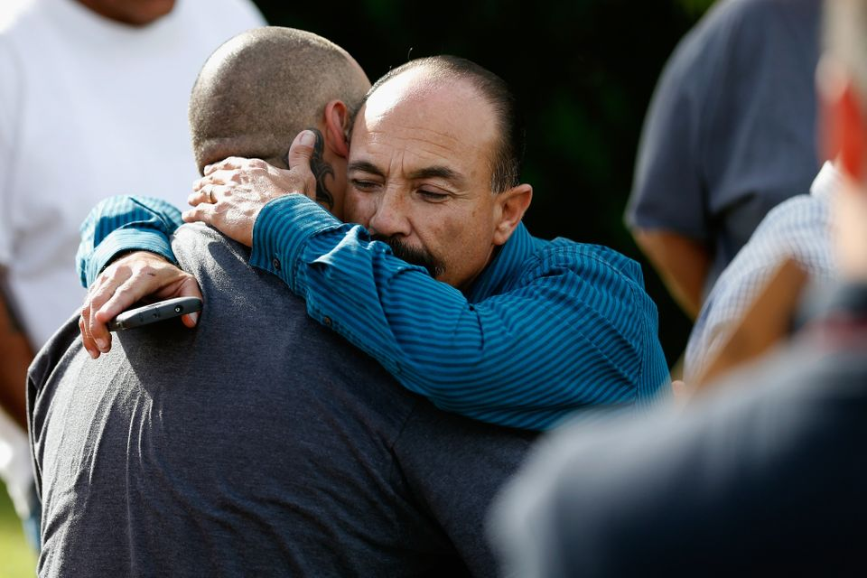 SAN BERNARDINO, CA - DECEMBER 03:  Jesus Gonzalez (L) and Pastor Ernie Ceballos (R) hug outside the crime scene where the sus