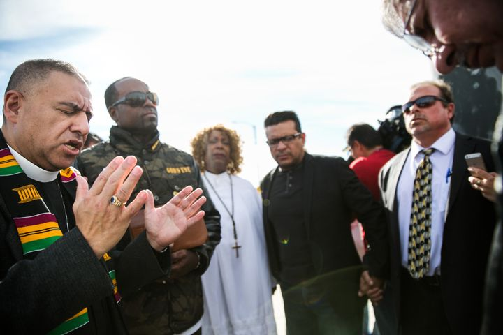 Pastor Juan Carlos Mendez, left, leads a prayer for the victims of the mass shooting at the Inland Regional Center, during a