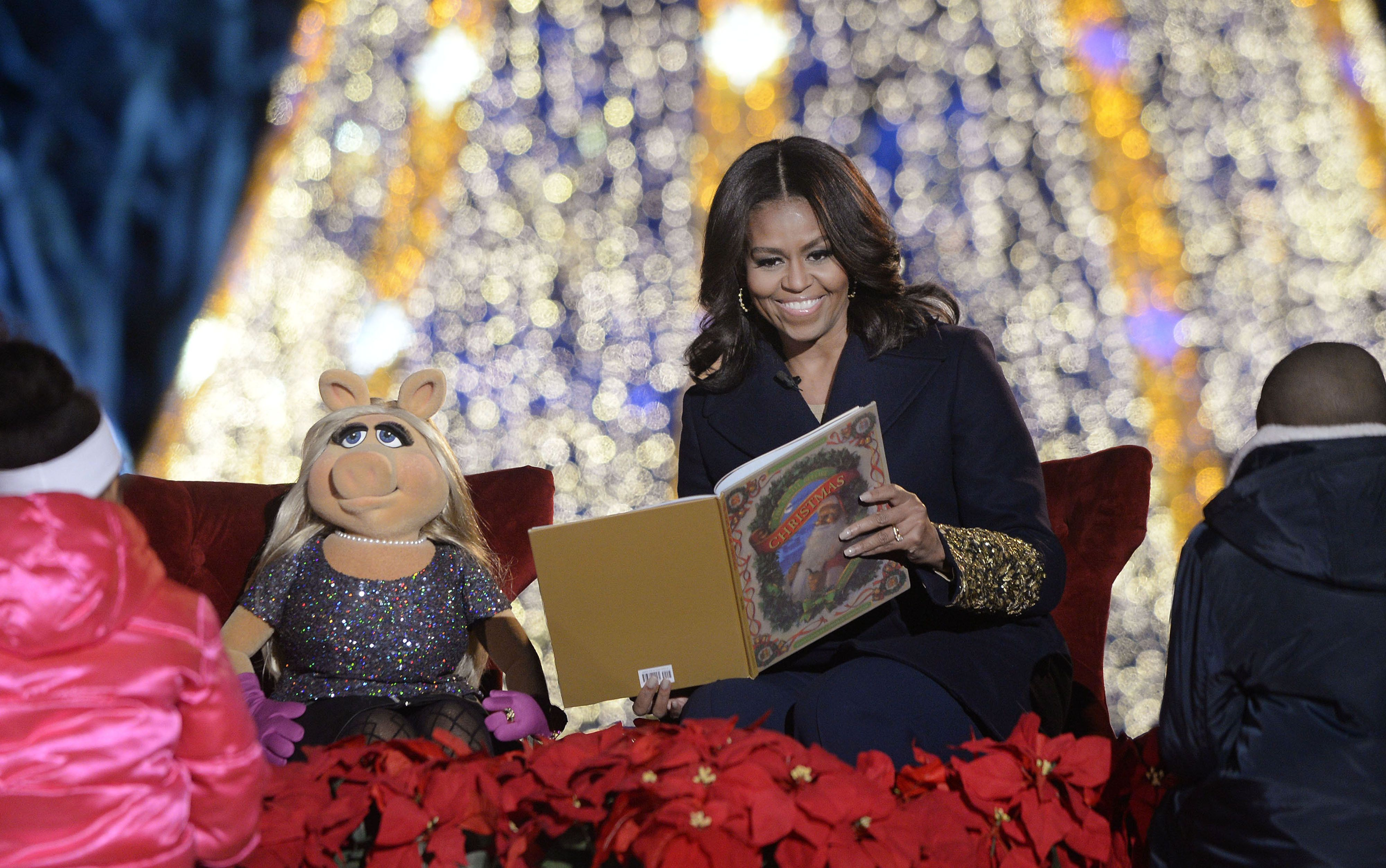 first lady Michelle Obama, right, and Muppets character Miss Piggy read a book to children during the National Christmas Tree lighting ceremony on the Ellipse near the White House in Washington, D.C., U.S., on Thursday, Dec. 3, 2015. In 1923 President Calvin Coolidge lit the first National Christmas Tree, a 48-foot balsam fir tree decorated with 2,500 electric bulbs in red, white and green. Photographer: Olivier Douliery/Bloomberg via Getty Images