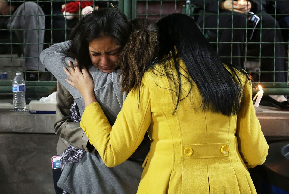 Faith Rodriguez is comforted as she cries during a vigil at the San Manuel Stadium to remember those injured and killed durin