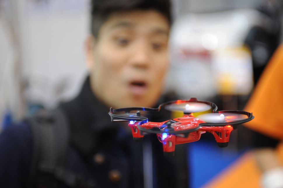 A miniature drone in flight at the International Robot Exhibition.