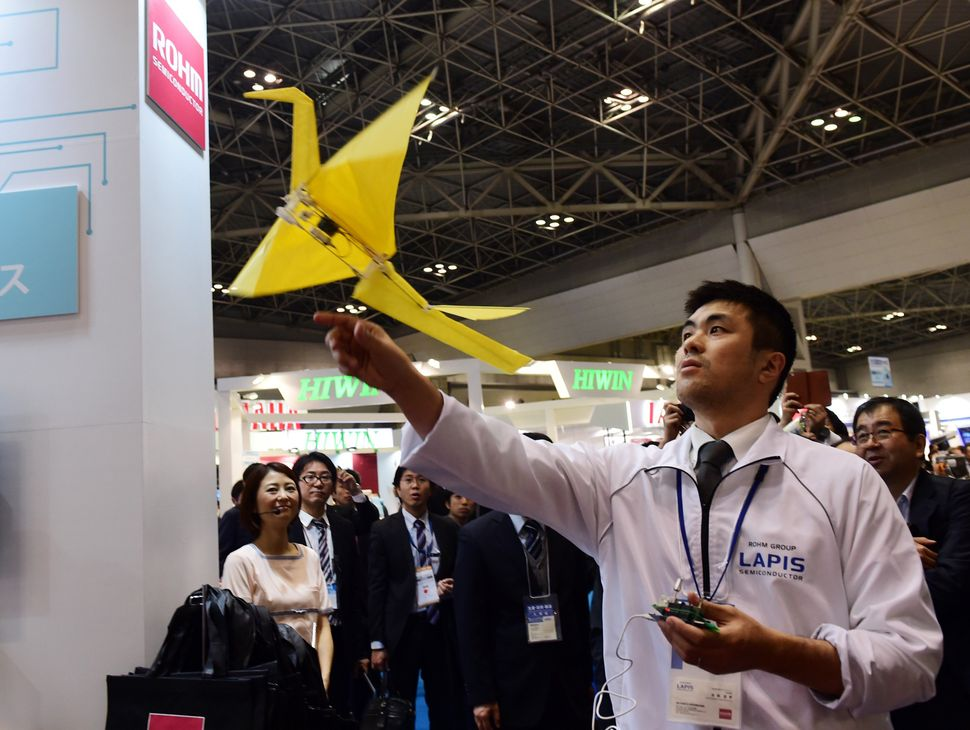 "An employee of Japanese electronics parts maker Rohm demonstrates remote-controlled flying paper crane ""Origami."""