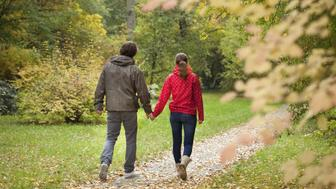 Couple on walk along path covered with leaves