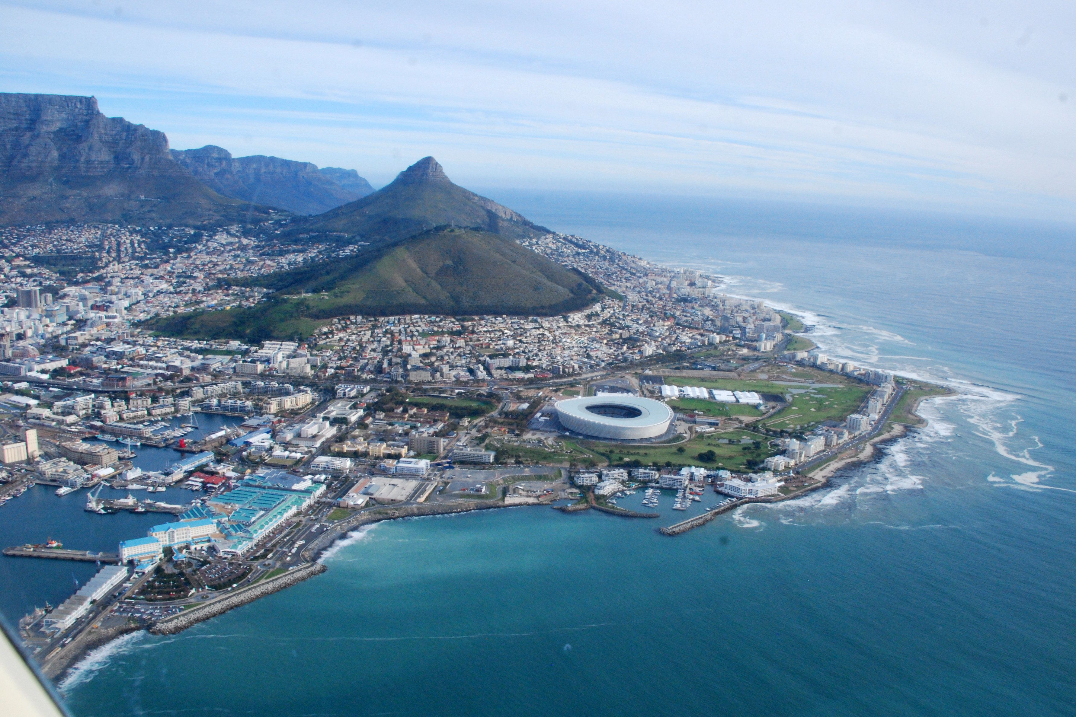 Aerial shot of Cape Town with V&A Waterfront, Signal Hill and Green Point Stadium at backdrop.
