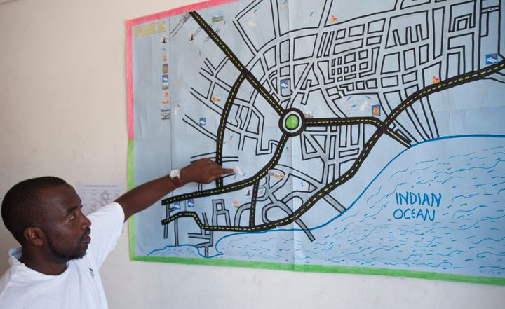 Bakari Hatib points out known heroin hotspots on a map used by The Omari Project's outreach workers. He is one of several out