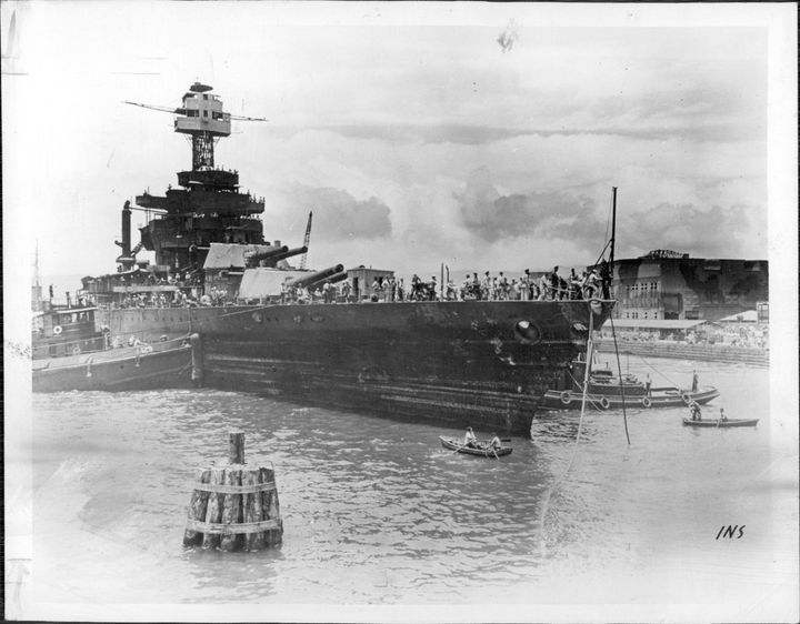 The USS West Virginia gets towed to drydock to start repairs in 1942.