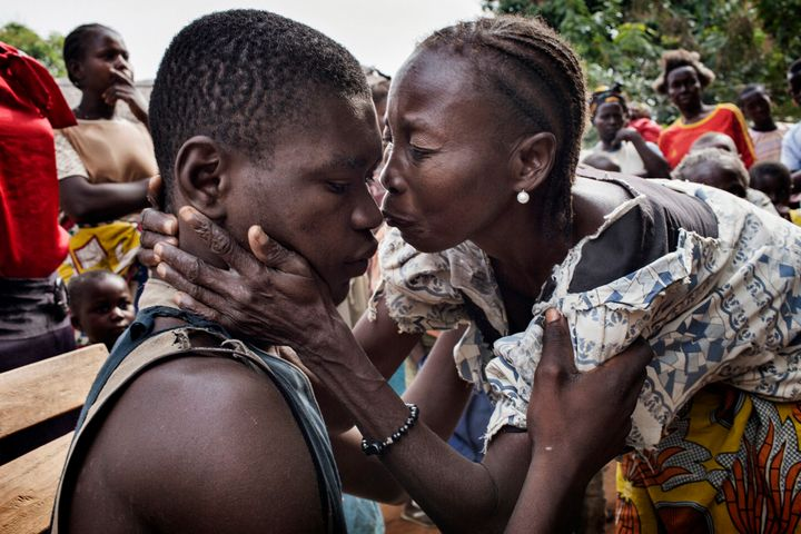 The mother of Eliam Fedongare greets him and celebrates as he arrives home with his father Jean de Dieux after the escaped th