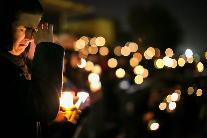 Community members gather during a candlelight vigil to honor the victims of the mass shootings at the Inland Regional Center