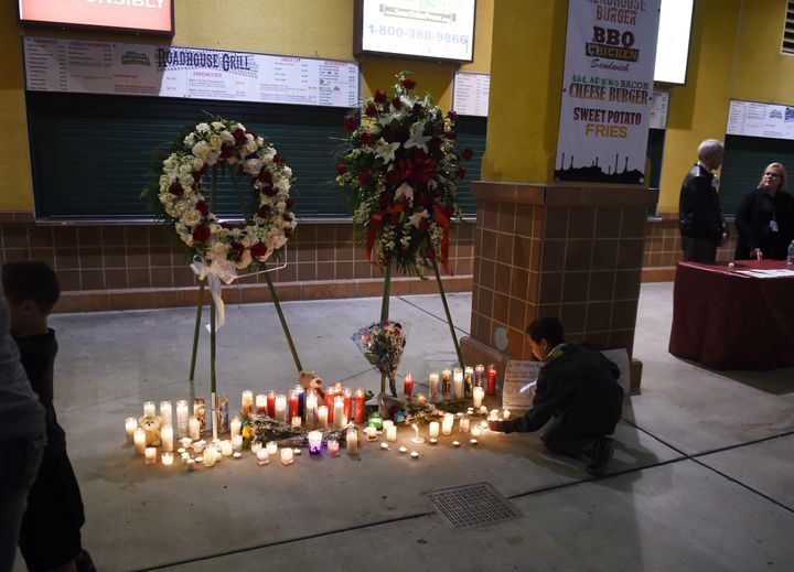 A boy leaves a candle at a memorial at a candlelight vigil at the San Manuel Stadium in San Bernardino, California, December