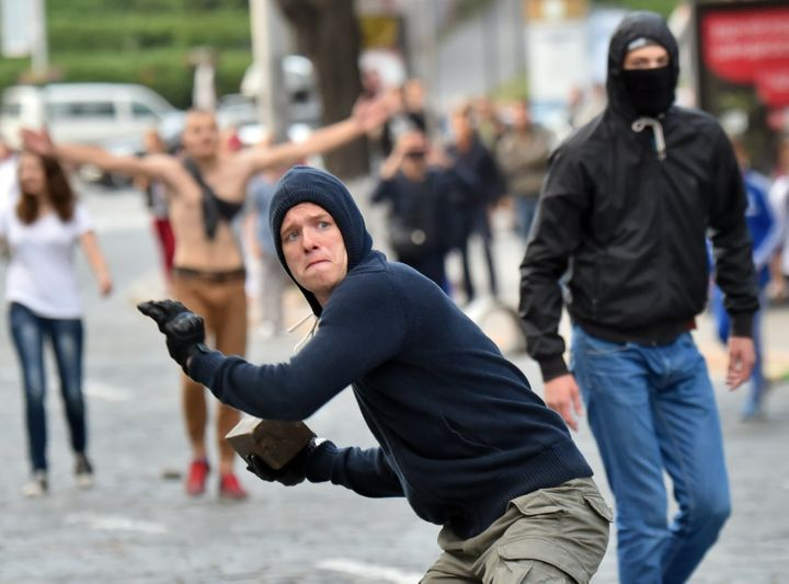 A Ukranian soccerfan readies to lob a brick towards police separating them from fans of another team priorto thei