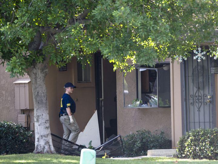 An FBI agent enters the attackers' residence in San Bernardino, California, Dec. 3, 2015.