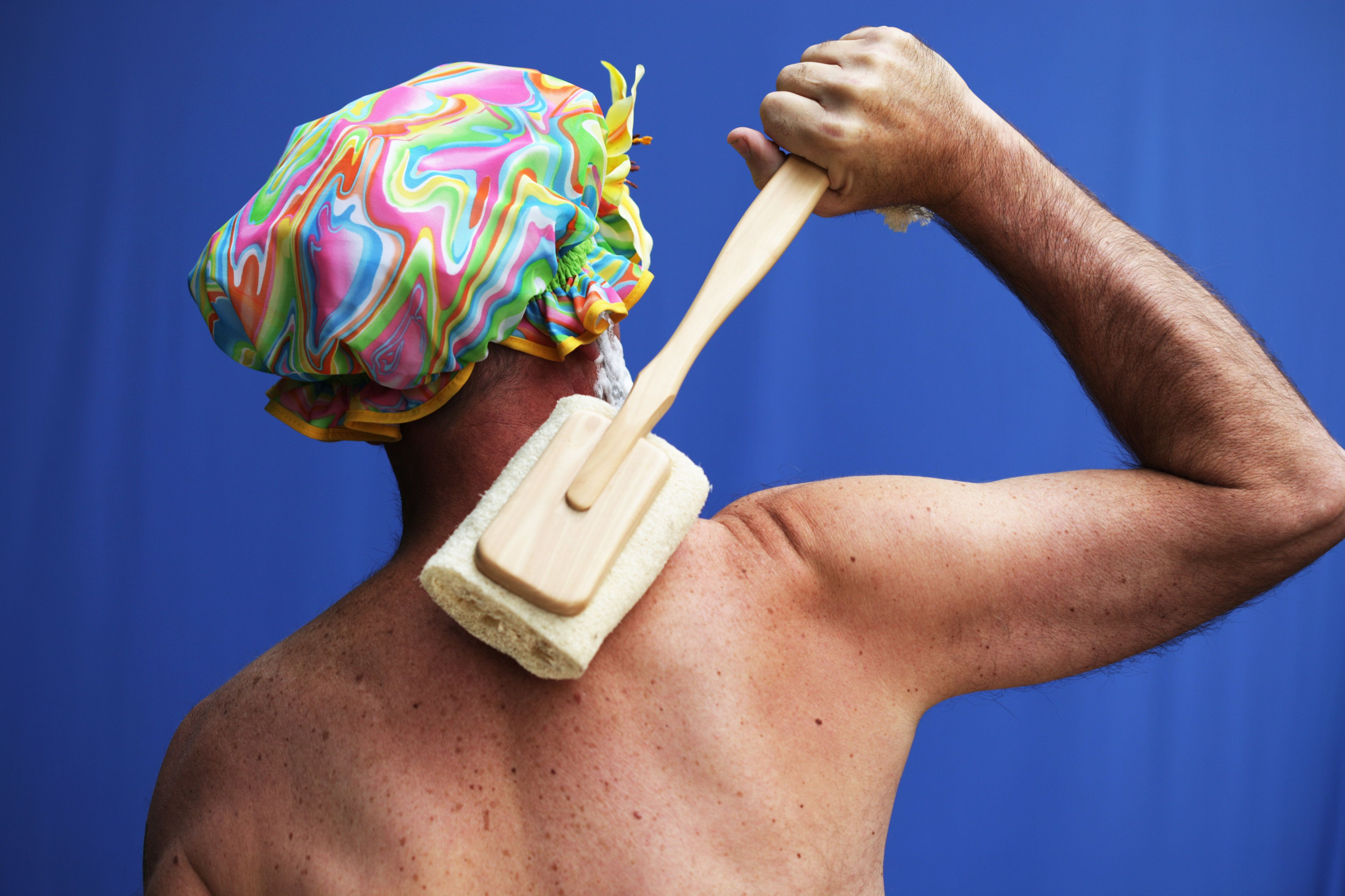 Man with retro shower cap washing his back with loofah