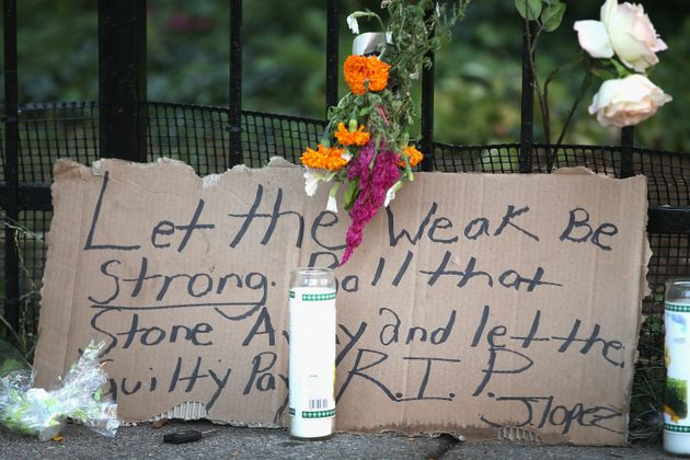 A memorial sits on the edge of the sidewalk outside the Uptown Baptist Church near where the victims...