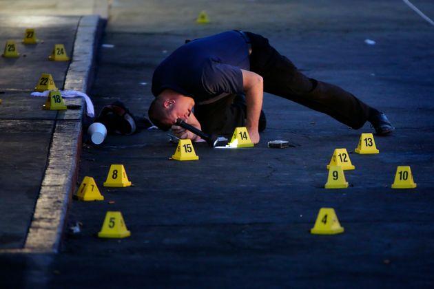 San Bernardino police detective B. Lewis investigates on July 8, 2014 a fatal shooting incident that...