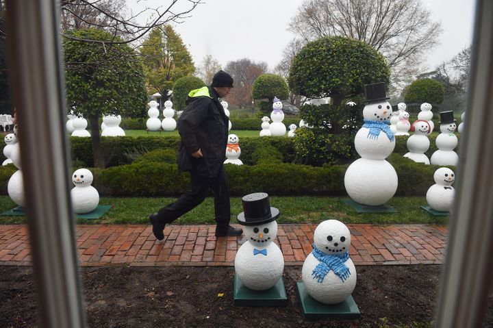 """A secret service officers walks by """"snow people"""" at The White House on Dec. 2, 2015."""