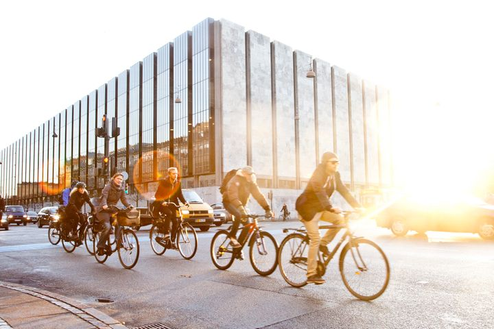 Cyclists ride bikes past the headquarters of Denmark's central bank in central Copenhagen, Denmark.