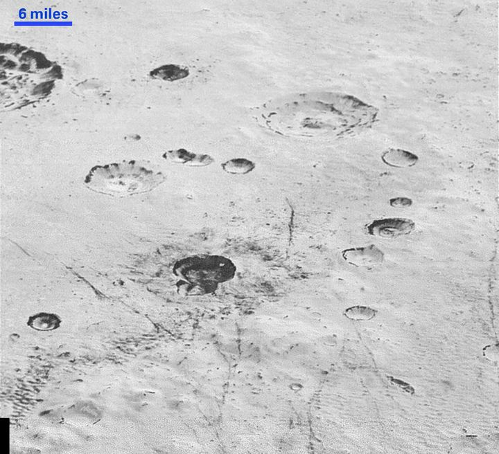 This image reveals new details of Pluto's rugged and icy cratered plains, including layering in the interior walls of craters