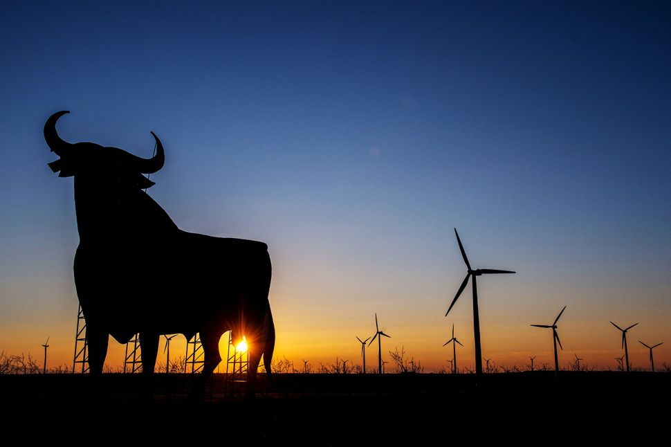 Wind turbines spin next to a giant bull advertisement for the Bodegas Osborne SA winery at a wind farm on Feb. 19, 2015, near